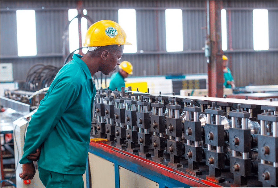 man inspecting product manufacturing line